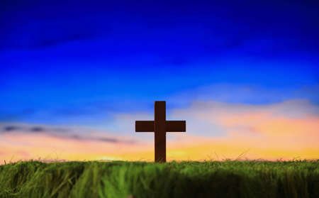 cross silhouette on grass with sunset background Stock Photo - 12527381