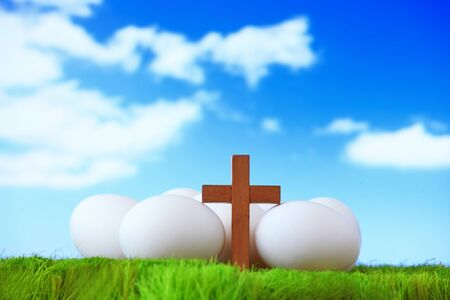 white eggs and wood cross on grass with blue sky, concept for easter photo