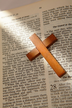 wooden cross on a old bible with the light from window photo