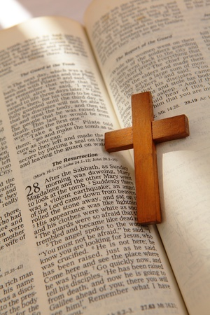 bible and cross: wooden cross on a old bible with the light from window