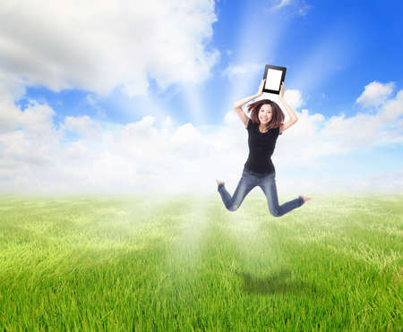 Happy Girl Jump and show touch pad computer on the meadow with blue sky and white cloud, for cloud computing concept photo