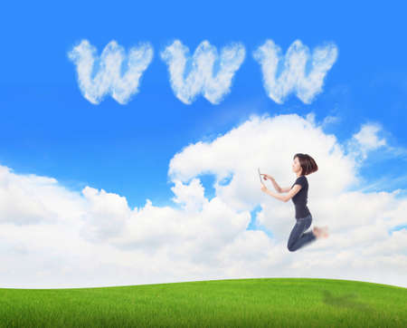 Young beauty happy jump and using tablet pc in the air on meadow with www cloud sky background , model is a cute asian, for cloud computing concept photo