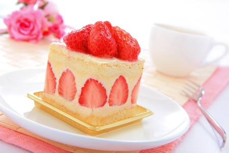 Dessert - sweet cake with strawberry on a plate with rose background photo