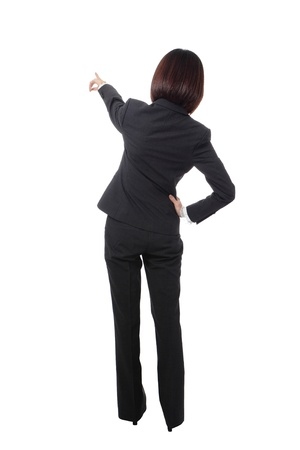 hands behind back: full length Business woman points finger at something in her back. Isolated on white background, model is a asian beauty Stock Photo