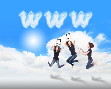 Happy Girl Jump and play touch pad computer in the air with blue sky and white cloud, , for cloud computing concept photo