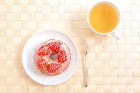 delicious strawberry doughnuts with green tea at afternoon photo