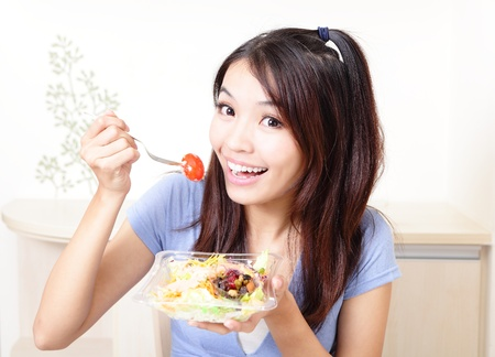 Young happy smiling woman with salad at home, model is a asian beauty photo