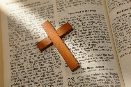 wooden cross on a old bible with the light from window