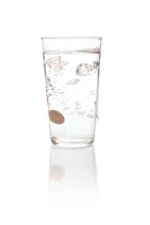 Water splashes when a coin money dropped in to a glass cup photo