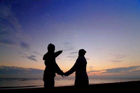 Silhouette of happy couple in love at sunset