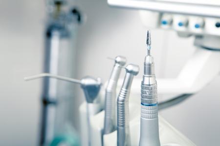 Metallic dentist tools close up on a dentist chair in Dentist Clinic (blue tone)