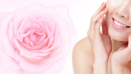 Close-up portrait of young beautiful woman smile mouth with pink rose flower background and touch her face, Model is a asian beauty photo