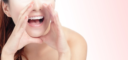 woman speaking: close up of woman mouth deliver message by whispering with pink background, model is a asian beauty