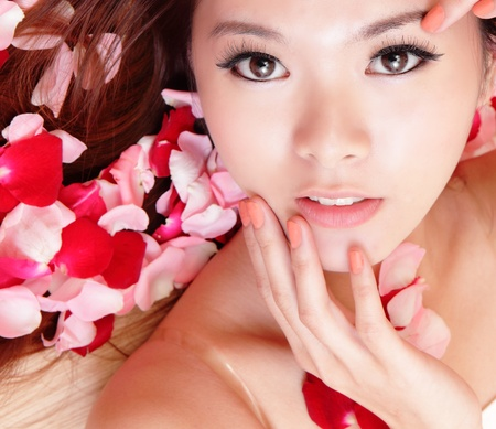 beauty Girl smiling face and hand touch her face close up with red rose background, model is a asian beauty photo