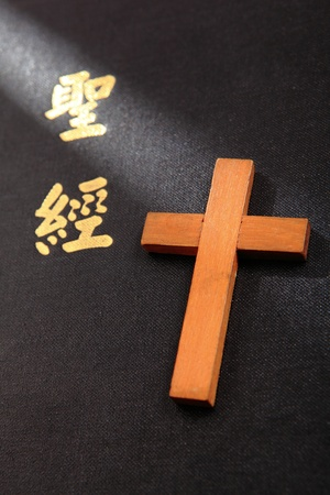 Chinese Bible Cover and wood cross in the morning sunshine photo