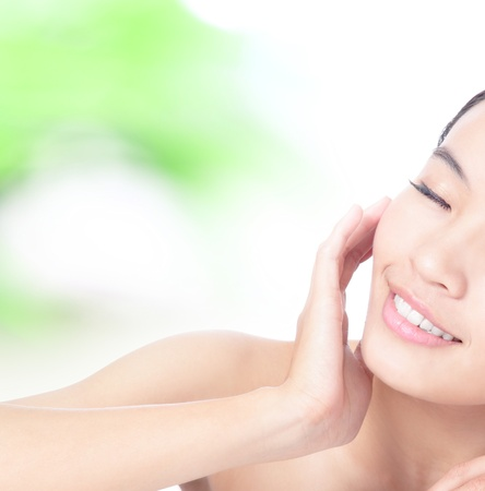 nature cure: Half beautiful woman Face and hand touch face with smile on green background, model is a asian beauty
