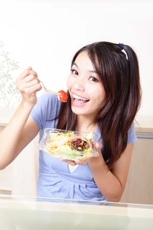 Young Girl Happy Eat salad at home, model is a asian beauty photo