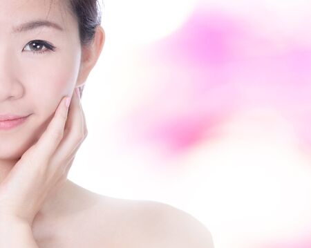 Woman Half smile Face and hand touch her perfect face for skincare with pink background, model is a asian beauty photo