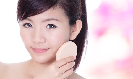 Young Woman applying foundation on face with cosmetic sponge on pink background, model is a asian beauty Stock Photo - 12984389