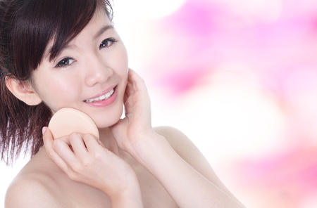 Young Woman applying foundation on face with cosmetic sponge on pink background, model is a asian beauty photo
