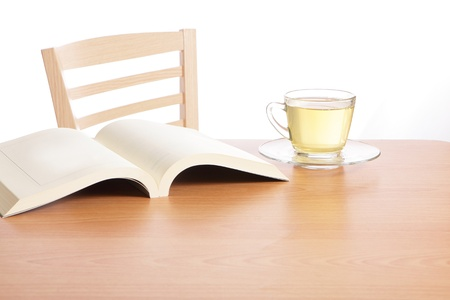 Tea and book on wood table in the morning photo