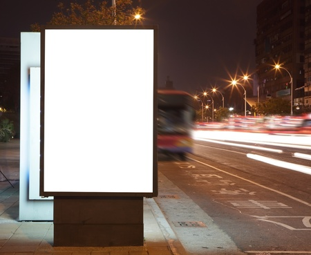 Blank billboard at night with car light trail in the city Street, white empty copy space is great for user photo