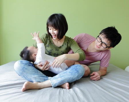 happy family, mother ,father and their baby with green background, model are asian family Stock Photo - 13103802