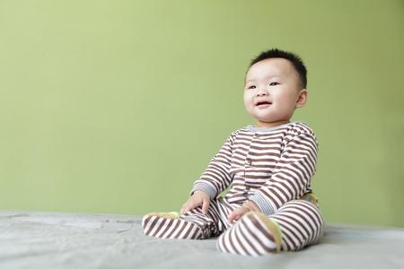 녹색 배경을 가진 귀여운 아시아 아기