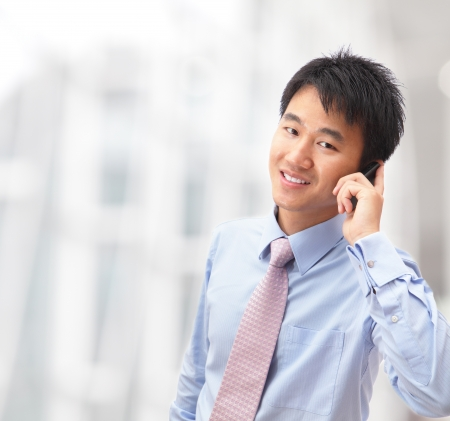 Asian male model: người đàn ông đẹp trai kinh doanh điện thoại di động nói tại tòa nhà văn phòng công ty của ông, mô hình là một nam châu Á