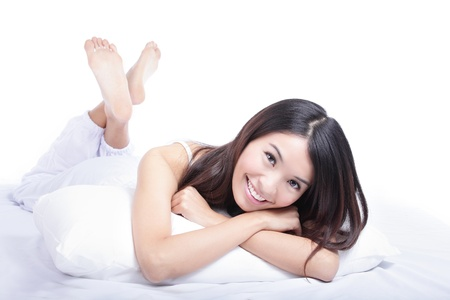 Close up of a happy young woman smile looking at something interesting while lying on the bed, isolated on white background , model is a asian girl photo
