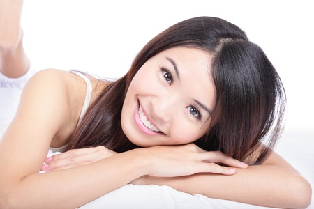 smile teeth: close up portrait of woman smile face lying on bed isolated on white background, model is a asian girl