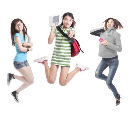 Emocionado grupo de estudiantes de la ni�a saltando - aislados en fondo blanco, modelo son los asi�ticos photo