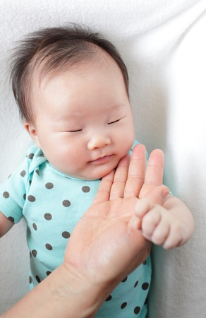 Baby sleep and mother touch her face at home photo