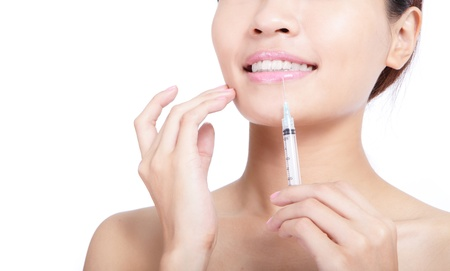 close up of woman recieving a botox injection in her lip isolated on white background, model is a asian beauty photo