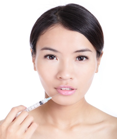 recieving: Beautiful woman recieving a botox injection in her lip isolated on white background, model is a asian beauty