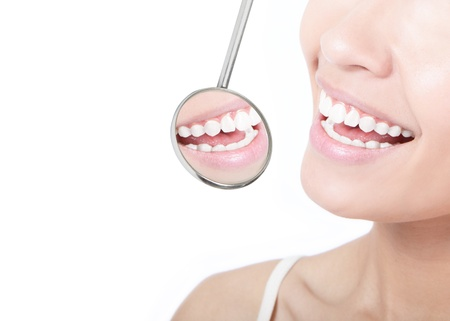 beauty treatment clinic: Healthy woman teeth and a dentist mouth mirror isolated on white background, model is a asian beauty Stock Photo