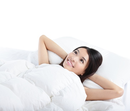 young woman smile and think while lying on the bed at home in the morning, isolated on white background , model is a asian girl photo