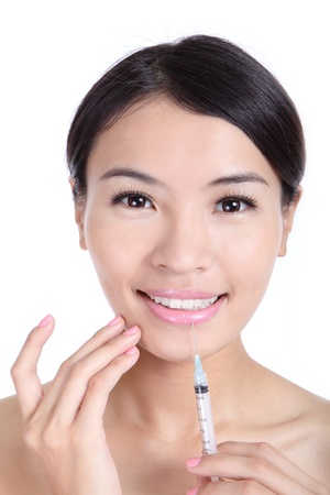 recieving: Beautiful woman smile recieving a injection in her lip isolated on white background, model is a asian beauty