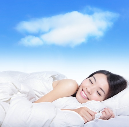 woman sleep: Portrait of a young girl sleeping on a pillow with white cloud over her , model is a asian beauty Stock Photo