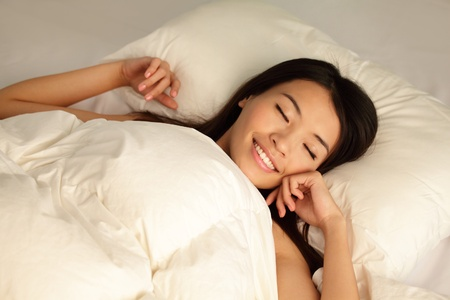 Young girl sleep peaceful with smile on home bed at night , model is a asian woman Stock Photo - 13389777