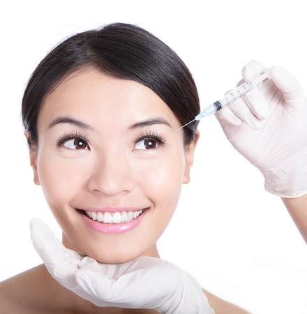 plastic surgeon: Cosmetic injection in woman face. Eye zone. Isolated on white background, model is a asian beauty