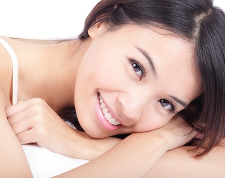 portrait close up of woman smile face in relax pose at home on bed, model is a asian beauty photo