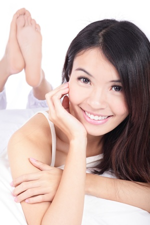close up portrait of happy girl smile face lying on bed at home isolated on white background, model is a asian beauty photo
