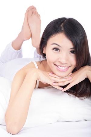 primer plano cara: feliz cara joven sonrisa de cerca mientras est� acostado en la cama, aislados en fondo blanco, modelo es una chica asi�tica