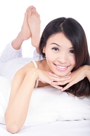 happy young woman smile face close up while lying on the bed, isolated on white background , model is a asian girl photo