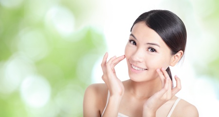 mano touch: Sorriso della giovane donna e il tatto concetto mano viso per la cura del corpo salute con sfondo verde della natura, il modello � una bellezza asiatica
