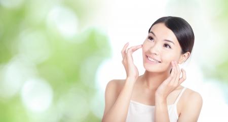 젊은 여자의 미소와 손 터치 얼굴 모습까지, 앞으로 모델은 아시아 아름다움 녹색 자연 배경 건강 바디 케어 개념합니다