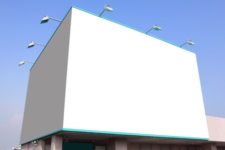 outdoor advertising: big white blank billboard with blue sky background