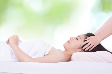 massage table: Portrait of a woman lying on a massage table in a health spa with nature green background, model is a asian girl