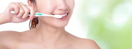 limpieza: cerca de una boca de la mujer y cepill�ndose los dientes con la naturaleza de fondo verde, el modelo es una chica asi�tica